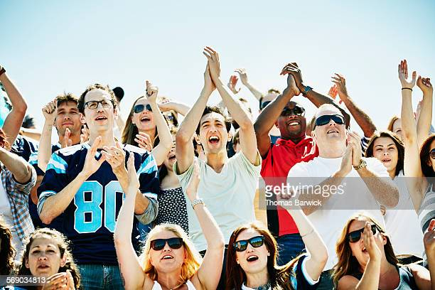 Football fans cheering in stadium during game