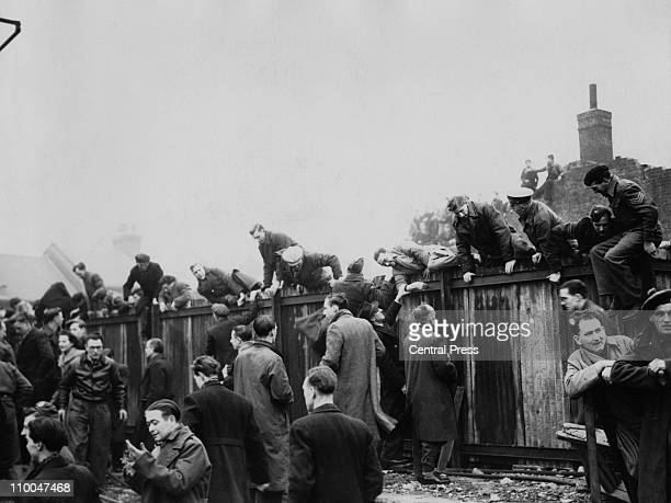 Football fans climbing over a fence at Upton Park football ground to watch the cup tie between West Ham and Arsenal London 5th January 1946