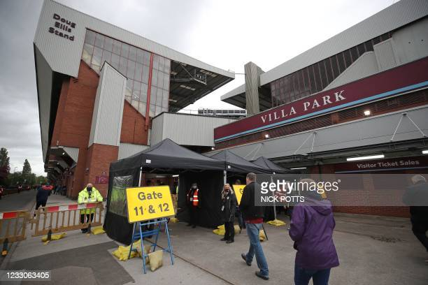 Football fans enter the stadium on a one-way system to enforce social-distancing ahead of the English Premier League football match between Aston...