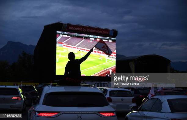 TOPSHOT Football fans follow the Austrian Cup final between FC Red Bull Salzburg and SC Austria Lustenau on a giant screen from their cars at a...