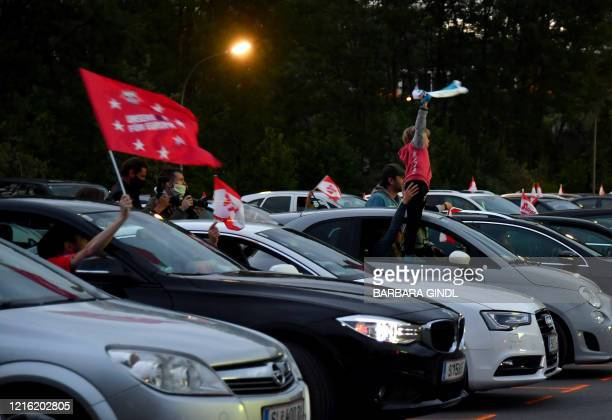 Football fans follow the Austrian Cup final between FC Red Bull Salzburg and SC Austria Lustenau on a giant screen from their cars at a drive-in in...