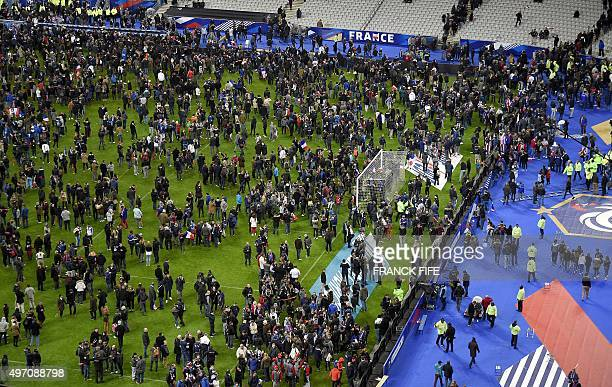 Football fans gather on the field of the Stade de France stadium following the friendly football match between France and Germany in SaintDenis north...