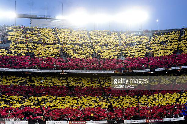 Football fans hold flags with Catalonia's colours prior to the Spanish Copa del Rey final football match Athletic Club Bilbao vs FC Barcelona at the...