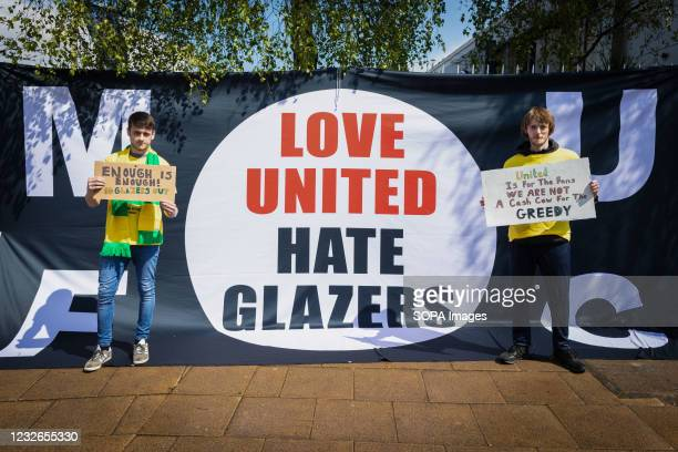 Football fans hold placards during a protest against the Glazer's ownership of Manchester United.