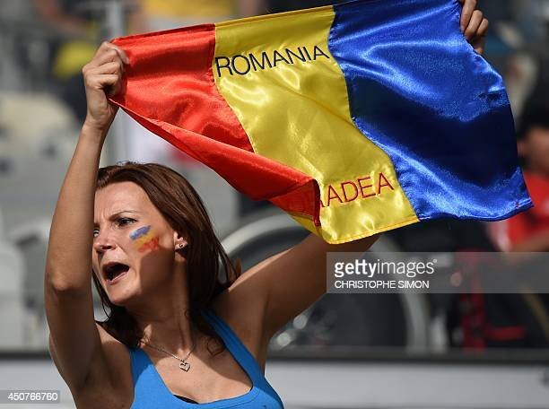 A football fans holds a flag of Romania during a Group H football match between Belgium and Algeria at the Mineirao Stadium in Belo Horizonte during...
