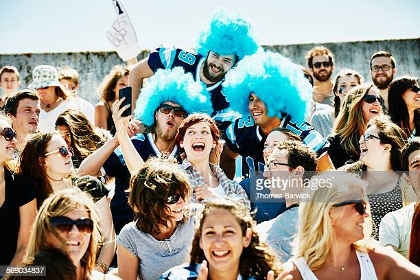 Football fans in stadium taking selfie during game