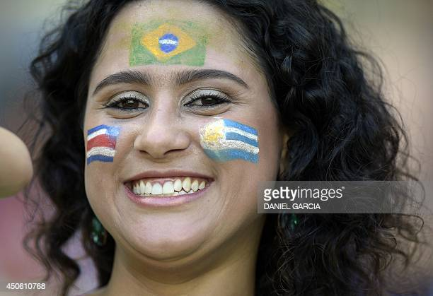 A football fans is made up in the colors of Brazil Uruguay and Costa Rica prior to a Group D football match between Uruguay and Costa Rica at the...