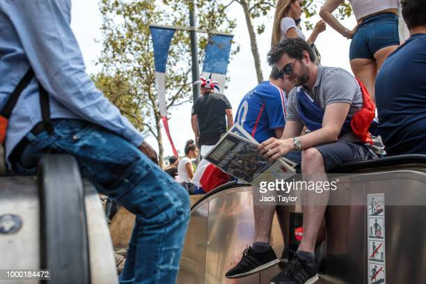 Football fans line the ChampsElysees before the French football team celebrate winning the World Cup with a parade on July 16 2018 in Paris France...