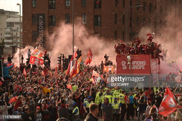 Football fans line the streets to see the Liverpool football team take part in an opentop bus parade around Liverpool northwest England on June 2...