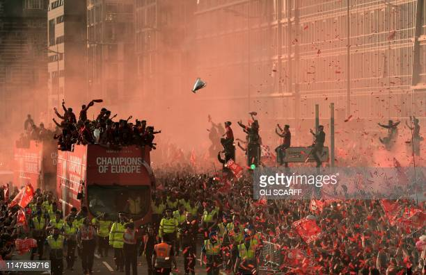 Football fans line the streets to see the Liverpool football team take part in an open-top bus parade around Liverpool, north-west England on June 2...