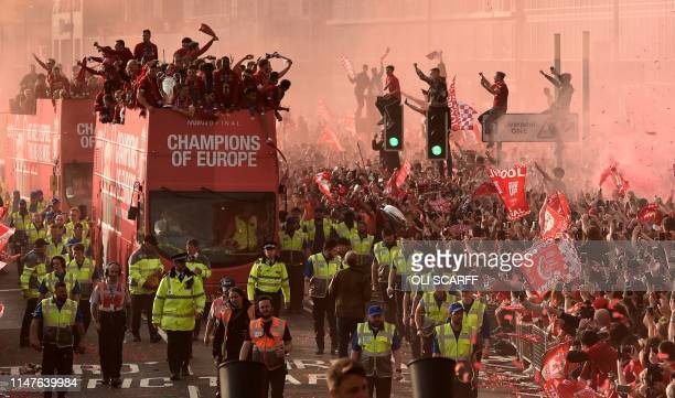 TOPSHOT Football fans line the streets to see the Liverpool football team take part in an opentop bus parade around Liverpool northwest England on...