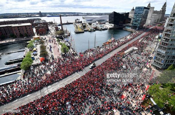 Football fans line the streets waiting to see the Liverpool football team take part in an opentop bus parade around Liverpool northwest England on...