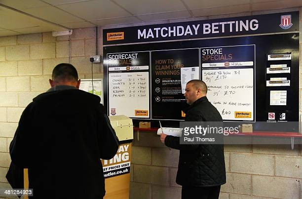 Football fans look at the matchday betting odds prior to the Barclays Premier League match between Stoke City and Hull City at Britannia Stadium on...