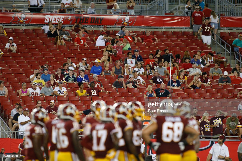 Football fans look on during the fourth quarter of an NFL preseason football game between the Tampa Bay Buccaneers and the Washington Redskins on August 31, 2017 at Raymond James Stadium in Tampa, Florida.