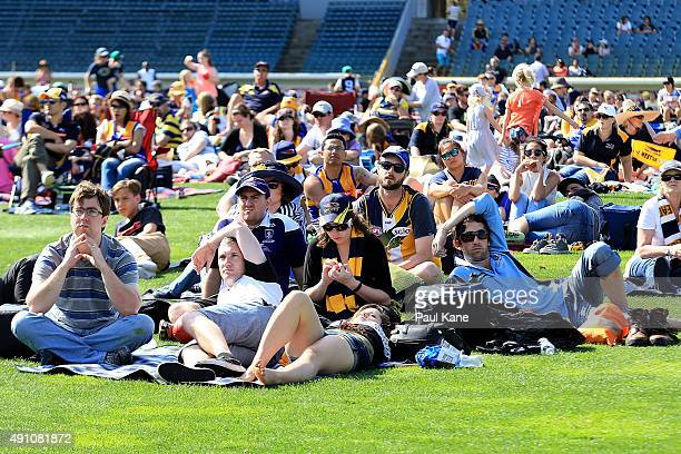 Football fans look on while watching the 2015 AFL Grand Final between the West Coast Eagles and the Hawthorn Hawks on the big screen at Domain...