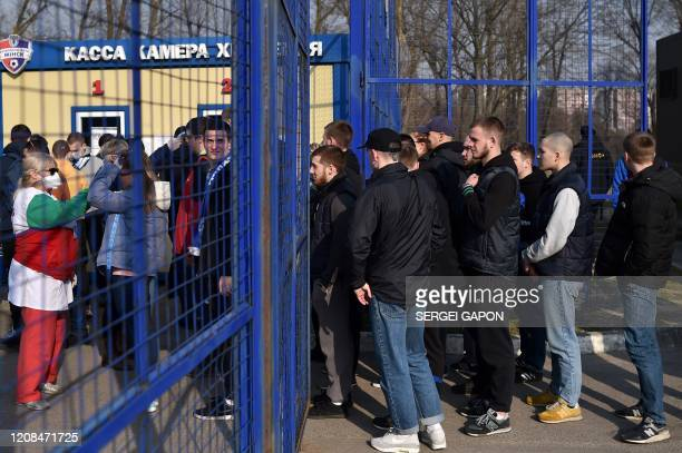 Football fans pass a medical control before the Belarus Championship football match between FC Minsk and FC DinamoMinsk in Minsk on March 28 2020 In...