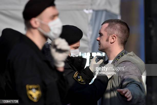 A football fans passes security control before the Belarus Championship football match between FC Minsk and FC DinamoMinsk in Minsk on March 28 2020...