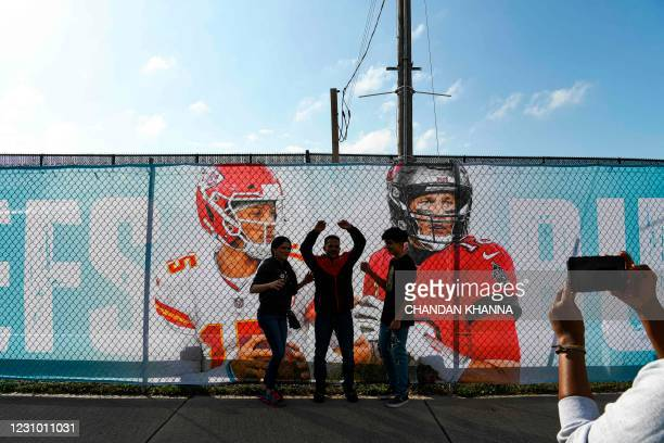 Football fans pose outside of the Raymond James Stadium a day before the Super Bowl match between Kansas City Chiefs and Tampa Bay Buccaneers in...