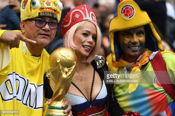 Football fans pose with a replica of the FIFA 2018 World Cup trophy before the Russia 2018 World Cup Group A football match between Russia and Saudi...