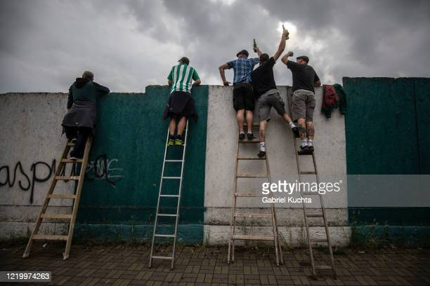 Football fans raise their drinks as they stand on ladders to peer over a wall as they watch a Czech First League match between Bohemians 1905 and FK...