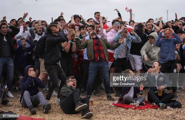 Football fans react as England go close to scoring as they watch the match inside the Lunar Beach Cinema on Brighton beach as England play Tunisia in...