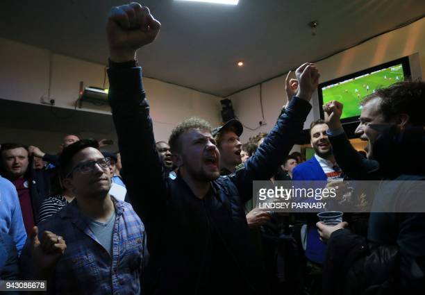 Football fans react as they watch the English Premier League football match between Manchester City and Manchester United in a pub near the Etihad...