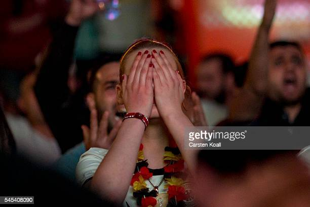 Football fans reacts in the end of the 2016 UEFA European Championship match between Germany and France at a public viewing area on a large outdoor...