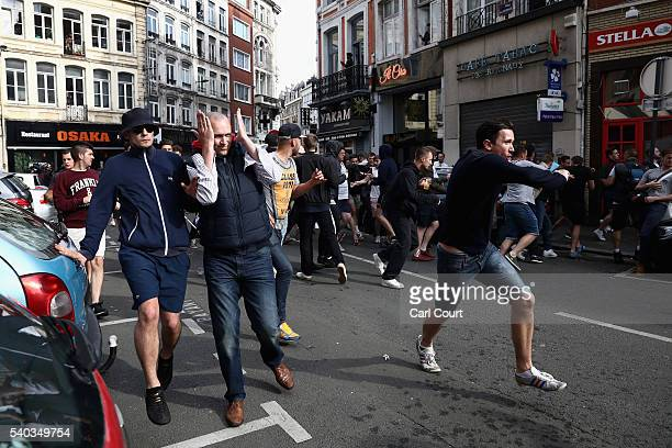 Football fans run through the streets as they clash with other fans on June 15 2016 in Lille France Football fans from around Europe have descended...