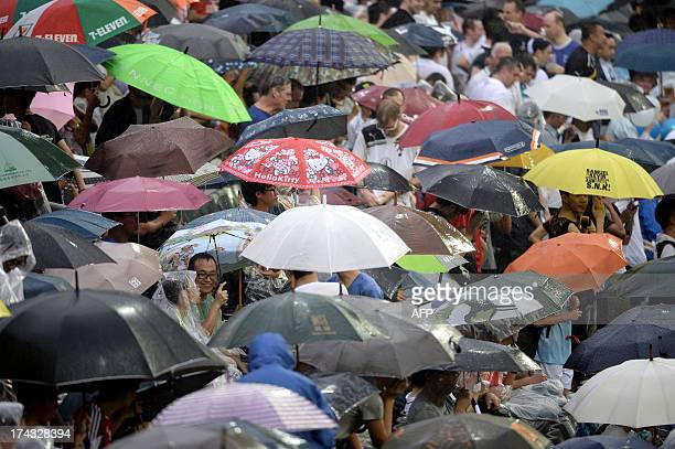 Football fans seek shelter under a sea of umbrellas as heavy rain delays the start of match between English football teams Tottenham Hotspur and...