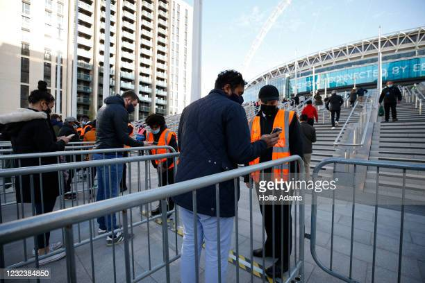 Football fans show their negative COVID-19 test results in order to enter Wembley Stadium on April 18, 2021 in London, England. 4000 local residents...