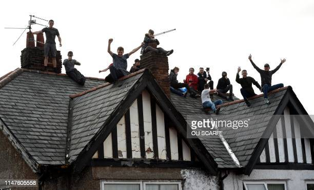 Football fans sit on the roof of a house as they wait to see the Liverpool football team take part in an opentop bus parade around Liverpool...