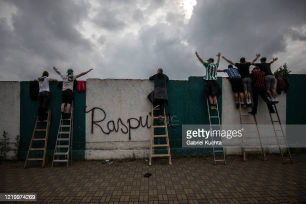 Football fans stand on ladders to peer over a wall as they watch a Czech First League match between Bohemians 1905 and FK Jablonec at Dolicek Stadium...