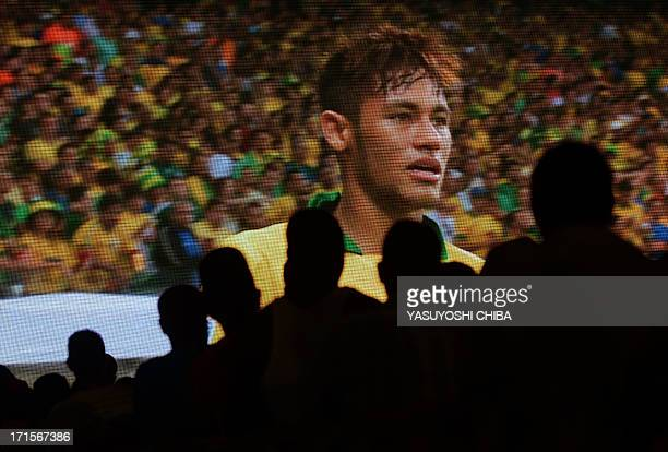 Football fans watch Brazil's forward Neymar playing against Uruguay their FIFA Confederations Cup Brazil 2013 semifinal football match held in Belo...
