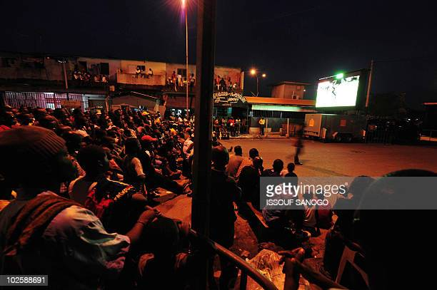 Football fans watch on a giant screen in a street of Abidjan the 'Black Stars' Ghana's national football team playing agaisnt Uruguay during a 2010...