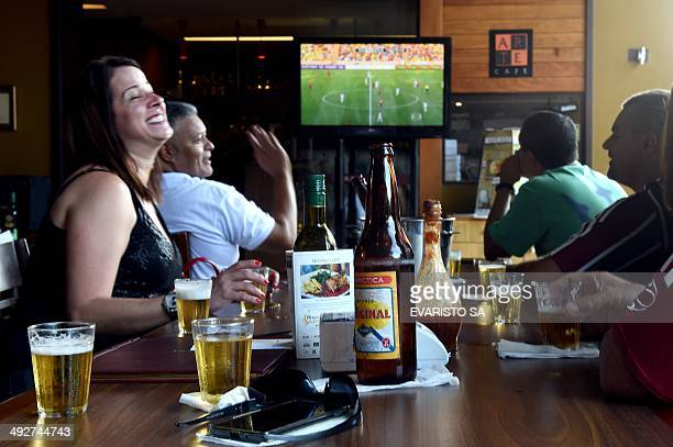 Football fans watch on TV the match between Fluminense and Flamengo drinking beer in a bar in Brasilia on May 11 2014 AFP PHOTO/Evaristo SA TO GO...