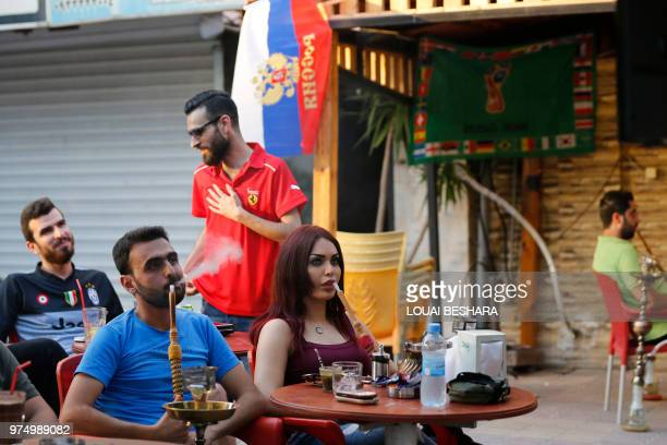 Football fans watch the 2018 World Cup football match Russia versus Saudi Arabia at the Moscow bar in Latakia western Syria on June 14 2018 With days...