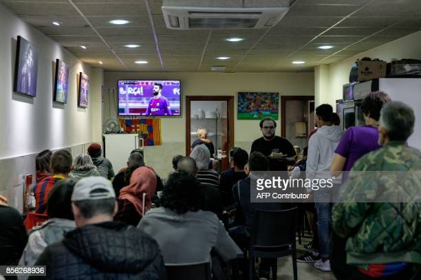 Football fans watch the match in a bar close to the Camp Nou after the decission of playing behind closed doors the Spanish league football match FC...