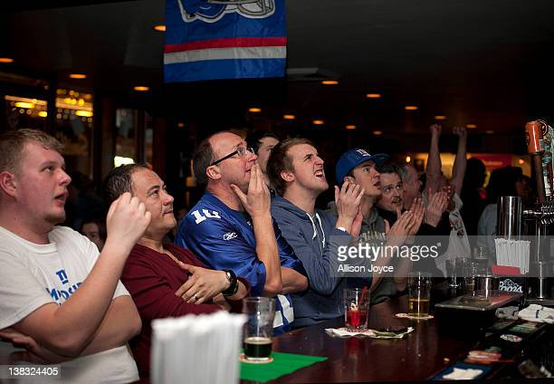Football fans watch the New York Giants take on the New England Patriots in Super Bowl XLVI at Smith's Bar on February 5 2012 in New York City The...