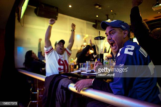 Football fans watch the New York Giants take on the New England Patriots in Super Bowl XLVI at Tonic Bar on February 5 2012 in New York City The...