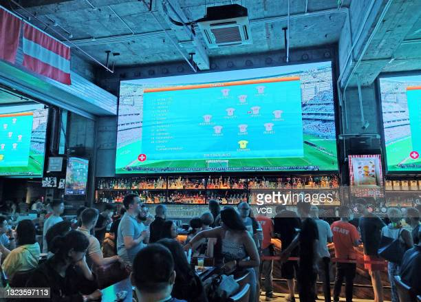 Football fans watch UEFA Euro 2020 Championship Group A match between Wales and Switzerland at a pub on June 12, 2021 in Shanghai, China.