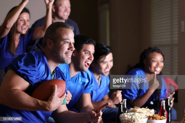 football fans watching the game at home on television. - sports jersey stock pictures, royalty-free photos & images