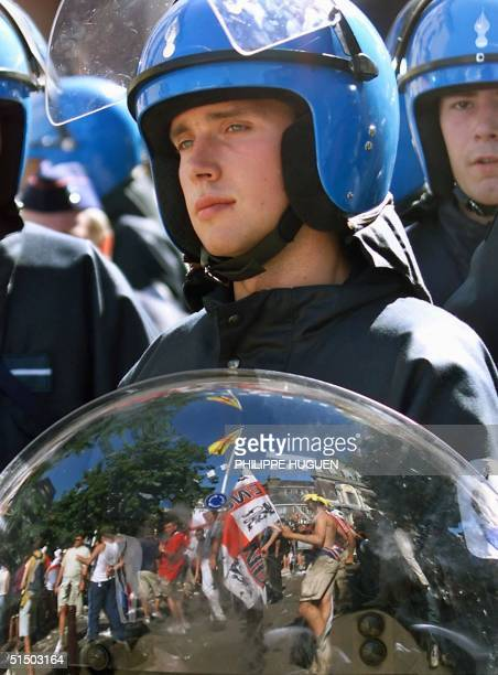 Football fans waving banners reflect in a policeman shield 17 June 2000, a few hours before the Euro 2000 first round match between England and...