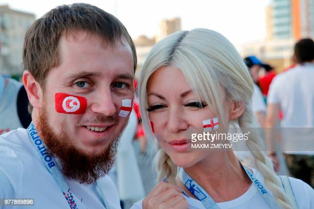 Football fans with a Tunisian and a English flag painted on their cheeks pose on their way to the Russia 2018 World Cup Group G football match...