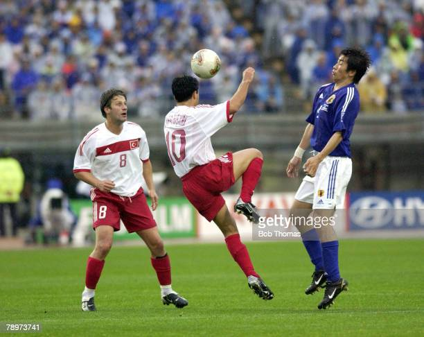 Football FIFA World Cup Finals Miyagi Japan 18th June 2002 Japan 0 v Turkey 1 Turkey's Yildiray Basturk jumps for the ball while watched by teammate...