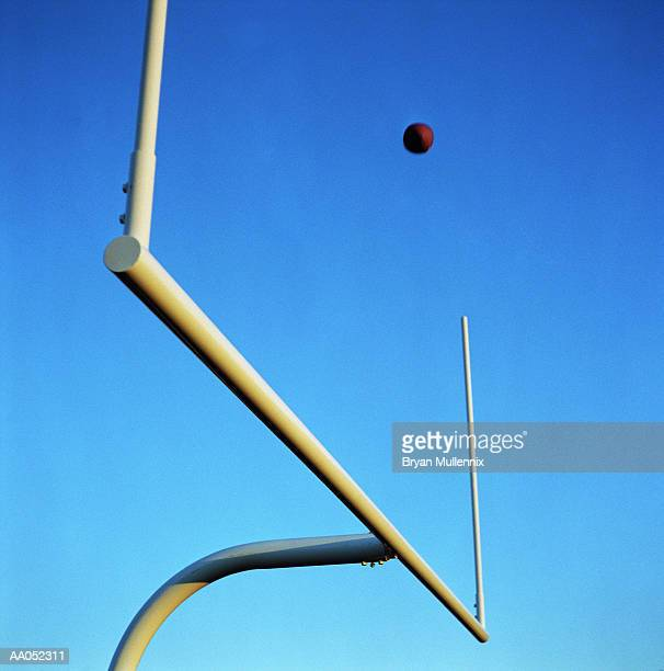 Football flying through field posts, view from below (selective focus)
