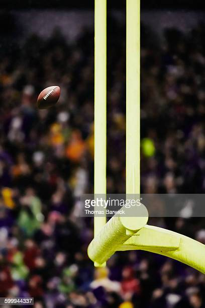 Football flying through goal posts in stadium