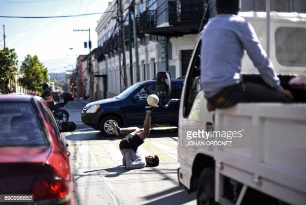 Football freestyler Michaell Arias performs in a street in the historic centre of Guatemala City on December 12 2017 / AFP PHOTO / Johan ORDONEZ