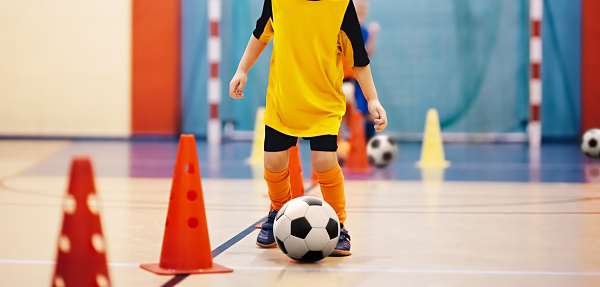 Football futsal training for children. Soccer training dribbling cone drill. Indoor soccer young player with a soccer ball in a sports hall. Player in orange uniform. Sport background 1049420470