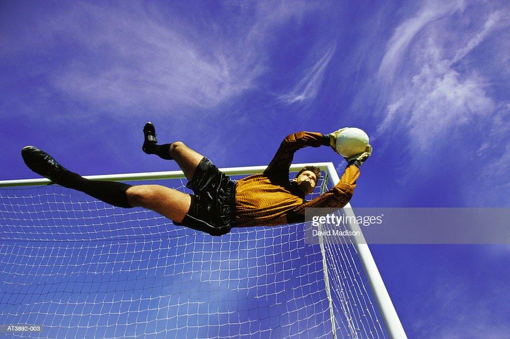 Football goalkeeper diving for ball (Digital Composite) : Stock Photo