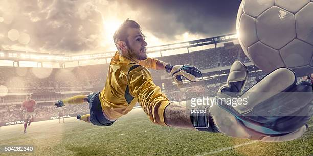 football goalkeeper diving to save ball during soccer match - goalkeeper stock pictures, royalty-free photos & images